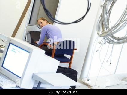 Woman working on laptop computer on chair, câbles accroché en premier plan Banque D'Images