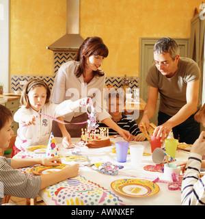 Famille rassemblée autour de la table de fête d'anniversaire Banque D'Images