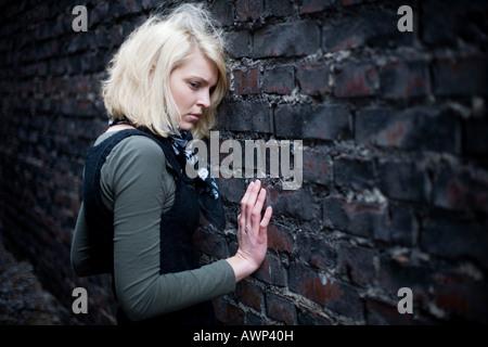 Femme blonde debout devant un mur de pierre