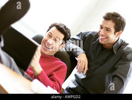 Homme assis avec les pieds sur le bureau en utilisant un ordinateur portable, deuxième homme regardant par-dessus Banque D'Images