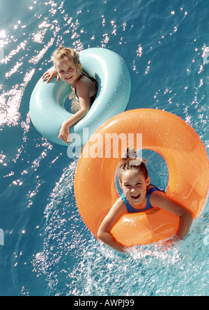 Deux petites filles en flottant dans l'eau gonflables joints toriques, high angle view Banque D'Images
