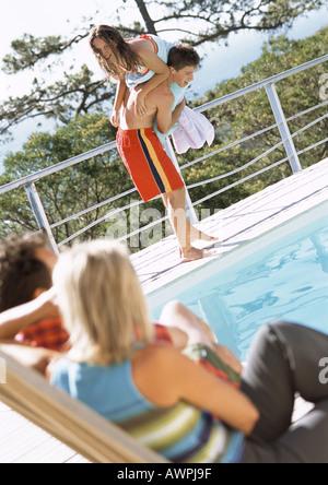 L'homme et la femme assis, regardant teenage boy picking up teenage girl au bord de la piscine Banque D'Images