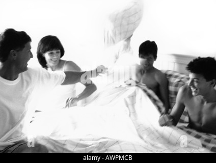 Family having pillow fight in bed, b&w Banque D'Images