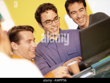 Trois hommes looking at laptop computer Banque D'Images