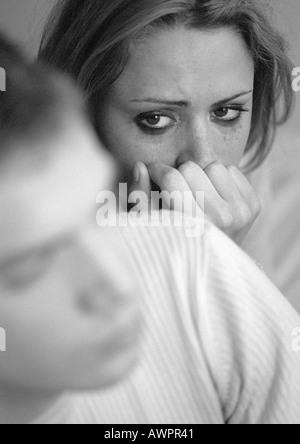 Femme en larmes avec la main contre la bouche, regardant l'homme, close-up, b&w Banque D'Images