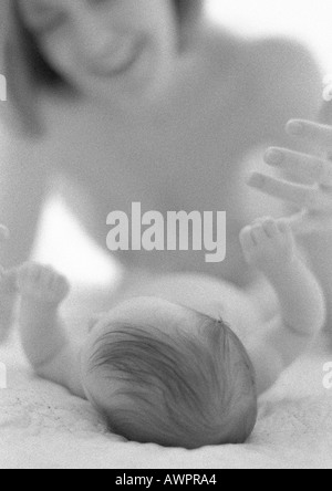 Bébé couché holding mother's finger avec part, b&w Banque D'Images