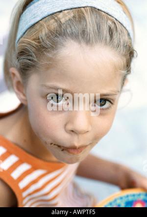 Petite fille avec du chocolat sur le visage, à la recherche en appareil photo, portrait. Banque D'Images
