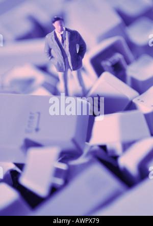 Petit jouet figure debout dans tas de touches du clavier, close-up Banque D'Images