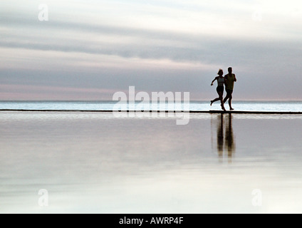 Couple running on beach Banque D'Images