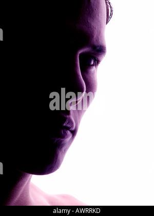 Visage d'un jeune homme sérieux en rétro-éclairage Banque D'Images
