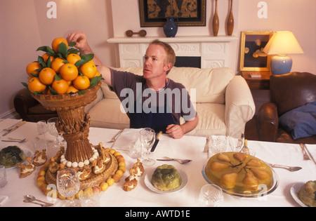 L'homme prépare une table pour dîner [partie] repas pour vos amis et votre famille HOMER SYKES Banque D'Images