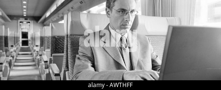 Businessman sitting in train using laptop, b&w, vue panoramique Banque D'Images
