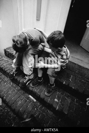 Deux enfants dans les escaliers, l'un tenant la tête dans les mains, b&w