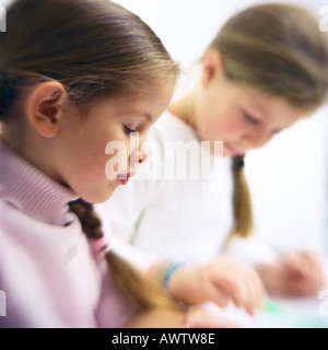 Deux filles assis à table, side view Banque D'Images
