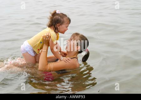 Jeune enfant jouant avec sa soeur aînée en eau peu profonde
