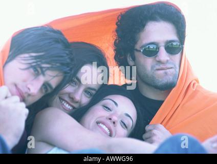Les amis enveloppé dans une couverture orange, close-up Banque D'Images