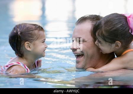 Père et filles en piscine Banque D'Images