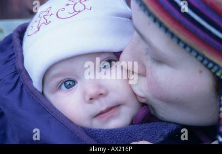 Mother kissing her 6 mois, sur la joue Banque D'Images