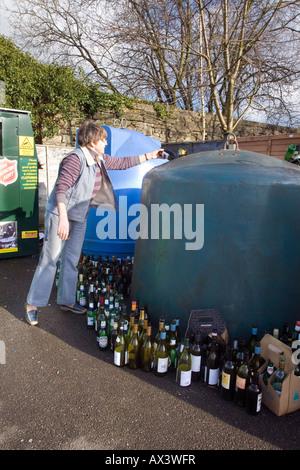 Femme de placer des bouteilles vides dans l'unité de recyclage Banque D'Images