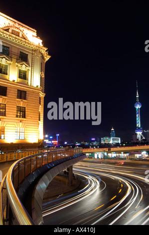 La Chine, Shanghai, Pudong New Area. La lumière de voiture traine sur le Bund et l'Oriental Pearl Tower illuminée Banque D'Images