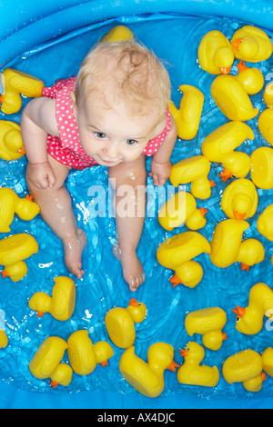 Petite fille en piscine avec des canards en caoutchouc Banque D'Images