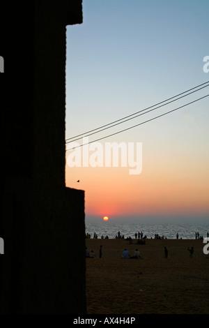 Les gens sur une plage bénéficiant d'un coucher de soleil Banque D'Images