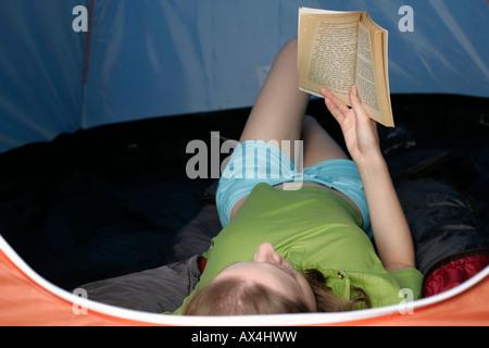 Jeune femme couchée dans une tente et la lecture d'un livre