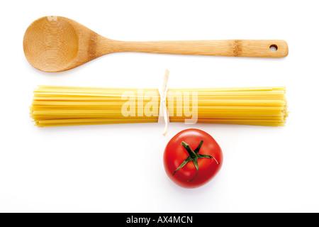 Paquet de pâtes, cuillère en bois et la tomate, elevated view Banque D'Images