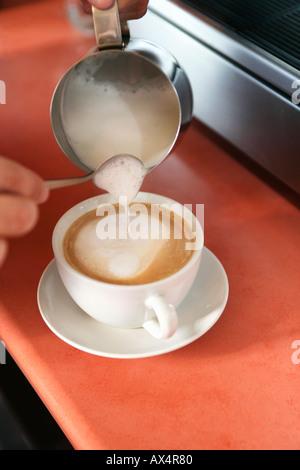Verser le lait à la vapeur Barista Banque D'Images