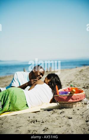 African couple having picnic on beach