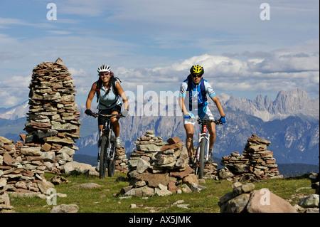 Les hommes et les vététistes à Stoanernen Mandlen, Hohen Reisch, Dolomites en arrière-plan, le nord de l'Italie, Banque D'Images