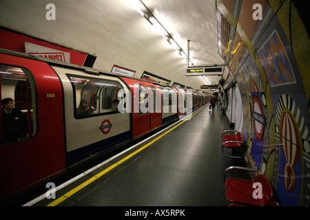 Logo du tube, tuiles de couleurs et de train en arrivant à Londres Arch, London, Angleterre, Royaume-Uni, Europe Banque D'Images