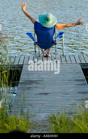 Rear view of woman sitting in armchair on pier Banque D'Images