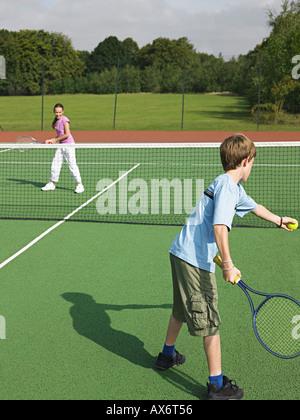 Frère et soeur à jouer au tennis Banque D'Images