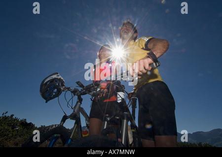 L'Autriche, Salzburger Land, Couple on mountain bikes laughing