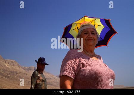 Femme portant un chapeau et un parapluie homme enduit de boue noire de la mer morte à Ein Gedi Sea of Spa resort Banque D'Images