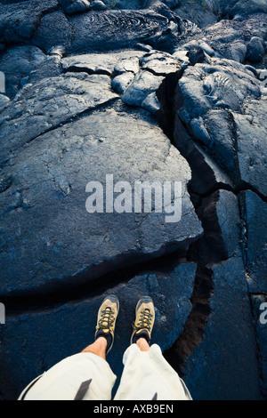 Un mans pieds et jambes debout sur la fissuration d'un bouleversement dans une coulée de Hawai i Volcanoes National Banque D'Images