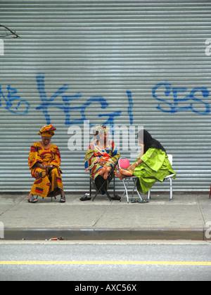 Trois femmes assises en face de volets d'un atelier fermé à la 125 rue à Harlem, USA, Manhattan, Harlem, New York Banque D'Images