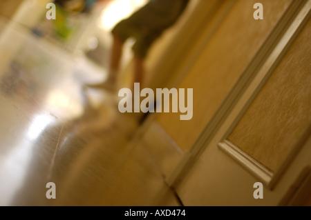Pieds et Jambes d'une petite fille dans un couloir appartement Banque D'Images