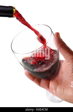 Le vin rouge est versé dans un verre de vin étant détenu par une main d'homme sur un fond blanc. Banque D'Images