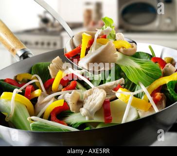 Sauté de légumes au wok étant brassé avec pleurotes, poivrons, pak choi et légumes Banque D'Images