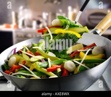 Sauté de légumes au wok étant brassé avec courgettes, brocoli, pousses de haricots et légumes Banque D'Images