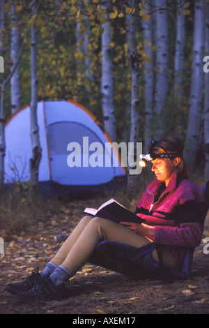 Femme lisant avec projecteur de camping dans les bois Banque D'Images