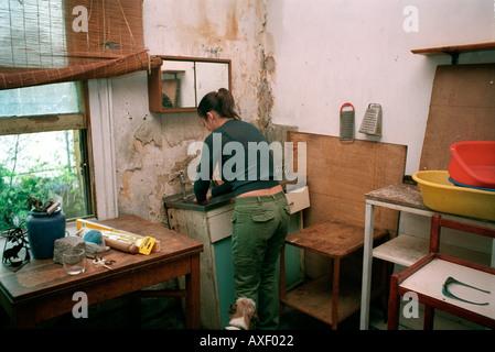 Jeune femme accroupie dans la décoration maison qui elle a grandi et a vécu pendant 30 ans.