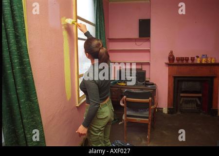 Jeune femme accroupie dans sa cuisine nettoyage maison qui elle a grandi et a vécu pendant 30 ans.