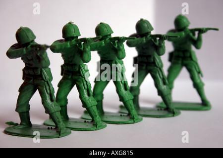 Ligne de cinq petits soldats en plastique armes de tir Banque D'Images