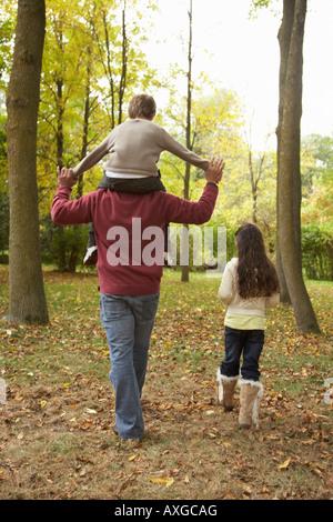 Le père et les enfants à pied à l'automne