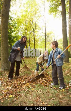 Grand-mère et ses petits-enfants le ratissage des feuilles Banque D'Images