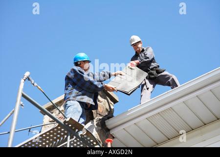 Les hommes qui travaillent sur le toit Banque D'Images