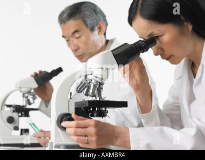 L'homme et la femme en laboratoire en utilisant des microscopes Banque D'Images